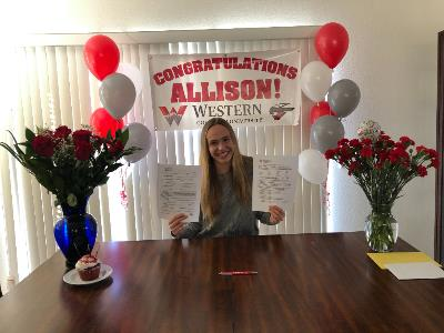 Allison with balloons signing with Western.